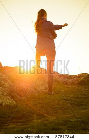 Young Fitness Woman Stretching in the Mountains at Sunset. Female Runner Doing Stretches Outdoor. Healthy Lifestyle Concept.