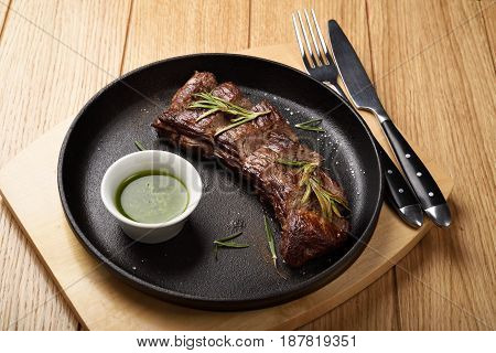 Prime Black Angus Skirt steak with sauce in a pan. Medium Well degree of steak doneness.