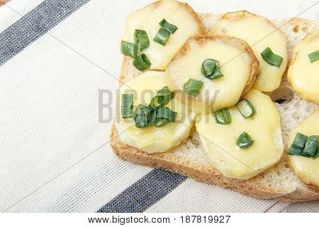 Appetizer of wheat bread potatoes cheese and green onions. There is room for text