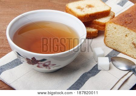 Black tea with sugar and cake with jam on a napkin and on a wooden background