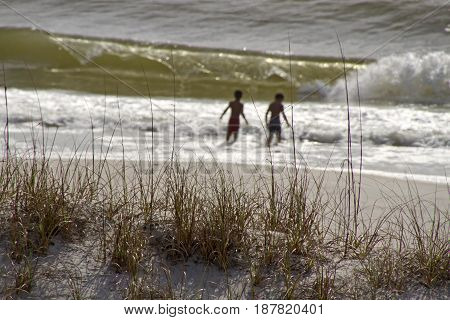 Blurred silhouettes of two young African American boys in swimming trunks wading into the ocean as a large wave crashes towards them on a partly sunny day
