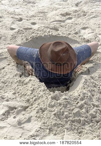A young man attempts to dig himself out of a hole in the sand that he's gotten himself into on a beach one sunny day