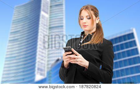 Businesswoman sending a sms outdoor