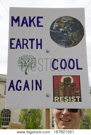 Asheville, North Carolina, USA - April 22, 2017: Man at a March For Science rally holds a political sign referring to Global Warming and current politics saying
