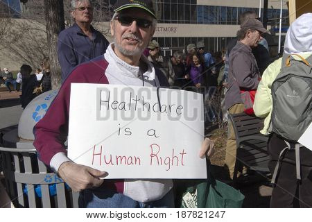 Asheville, North Carolina, USA - February 25, 2017: A man hold a sign at a crowded Affordable Care Act rally saying