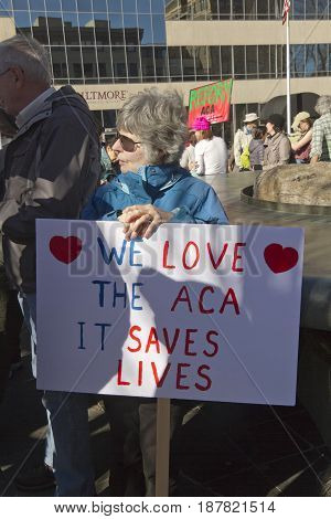 Asheville, North Carolina, USA - February 25, 2017: A woman holds a sign at a crowded Affordable Care Act demonstration that says