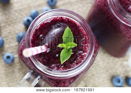 Blueberry smoothie in a glass jar with a sprig of mint