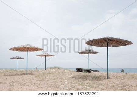 Row of sunshade umbrellas on sea beach. Tranquil view of the Mediterranean sea. Sunny day with clear blue sky. Minimalist scene. Location place: Turkey, Kemer.