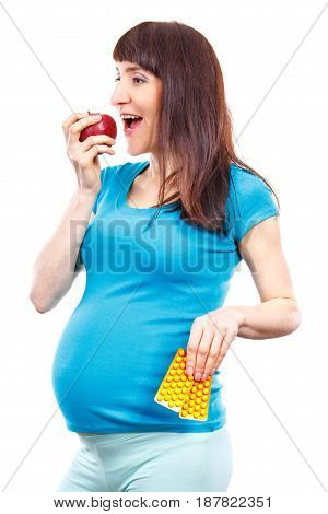 Happy Pregnant Woman Eating Fresh Apple And Holding Medical Pills Or Supplements, Choice Between Hea