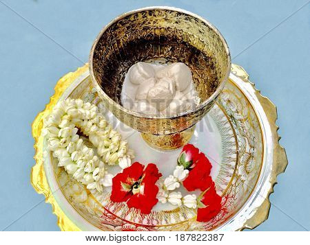 Songkran Festival Beautiful Jasmine Garland with Red Roses Blossoms and Soft Prepared Chalk in Porcelain Pedestal Dish for Songkran Festival on Thailand New Year.