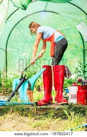 Female Farmer And Gardening Tools In Garden
