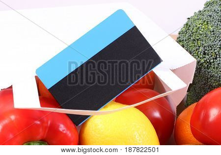 Contactless credit card and paper bag with fresh fruits and vegetables cashless paying for shopping