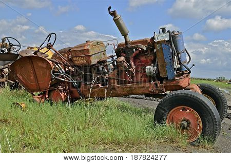 BARNESVILLE, MINNESOTA, September 14, 2014: The Massey Harris name on the rusty tractor disappeared when a merger of Massey Harris and the Ferguson Company farm machinery manufacturer occurred in 1953, to become Massey Ferguson.