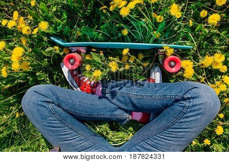 Bright And Colorful Skateboard And Female Feet In Sneakers