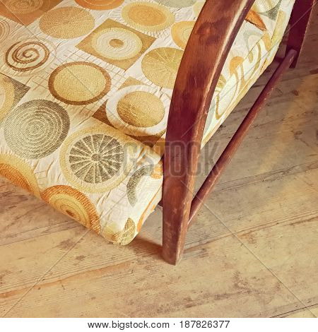 Detail of a vintage textile armchair on wooden floor. Retro style furniture.
