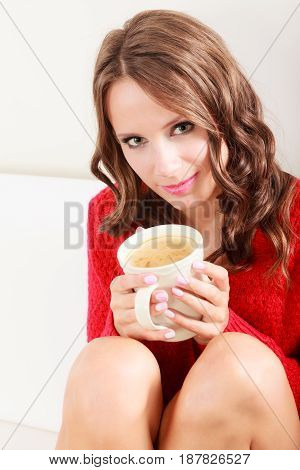 Attractive fall girl red autumnal sweater holding white mug with coffee warm beverage sitting on sofa at home. Woman warming herself relaxing top view
