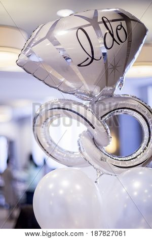 White and silver mylar engagement balloon that says