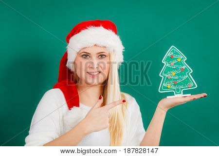 Enjoying cozy holiday interior seasonal accessories concept. Blonde young woman in Santa hat holding little decorative Christmas tree.