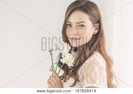Sweet girl in a white dress is holding a bouquet of white flowers in her hands. She is standing by the window.