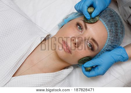 Beauty salon. Spa. Anti-aging facial massage with jade stones. Gua sha. Aesthetic facial treatment. Skin care. Smoothing wrinkles.