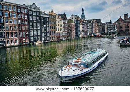 AMSTERDAM, NETHERLANDS - MAY 8, 2017: Canal cruise tourist boat in Amsterdam at Damrak canal and pier. Amsterdam, capital of the Netherlands, has more than one hundred kilometers of canals