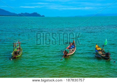 Three fishing boats floating on sea in sunny day