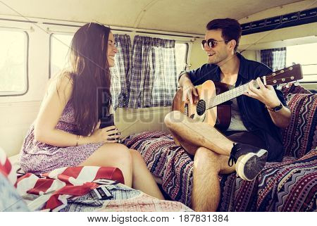 Man Playing Guitar with Woman in a Van Road Trip