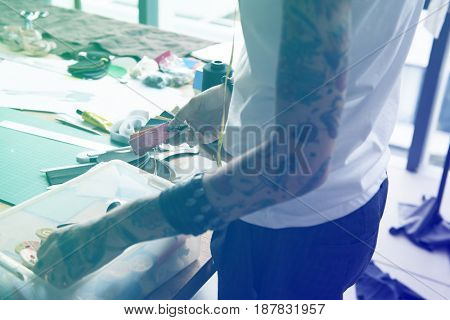 Fashion designer tattooed girl choosing material