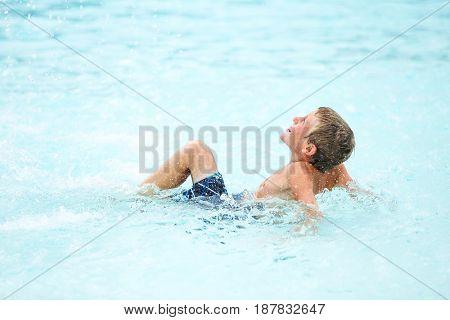 Boy playing at a waterpark pool