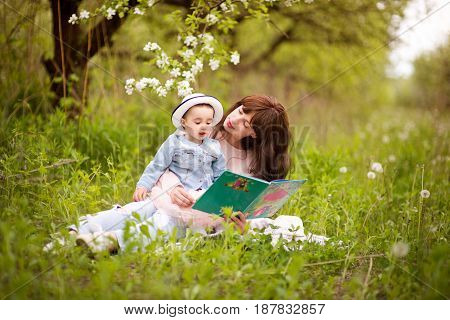 Mother reading a book with tales  to little daughter outdoors in the garden or the park