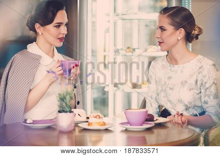 Two elegant young ladies in a cafe