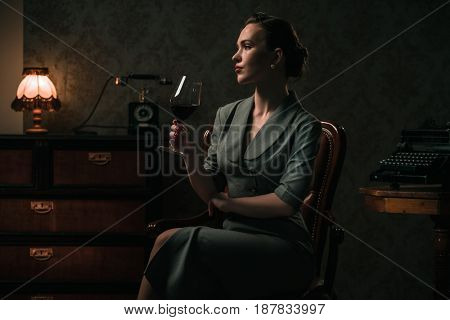 Beautiful woman with glass of wine in retro interior