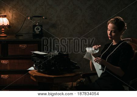 Beautiful woman destroying letter in retro interior