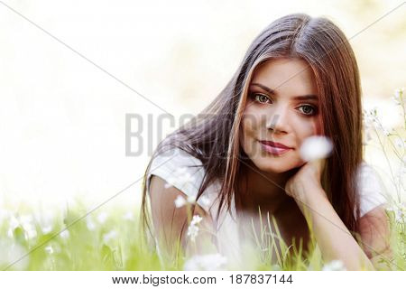 Pretty brunette girl laying on grass with white  flowers around her
