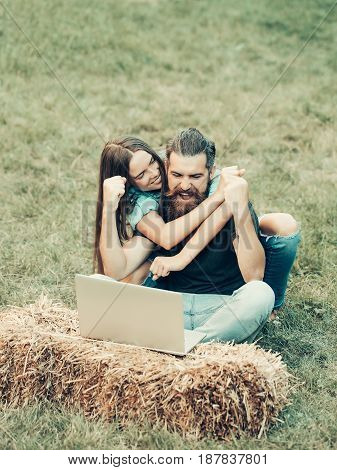 friends or brother and sister happy woman and man winner with laptop on hay sitting on green grass embracing on natural background outdoor