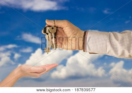 Businessman handing a key to success over a woman palm. a house in the background