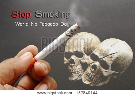 World No Tobacco Day Smokers hand with cigarette and skull on dark background.
