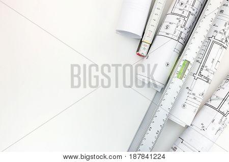 Rolls Of Architectural Blueprints, Spirit Level, Zigzag Ruler On White Background