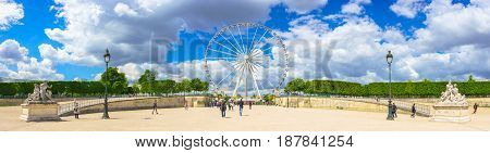 Paris France - May 2 2017: Panorama view of The Big Wheel at Place de la Concorde view from Tuileries Garden with the crowd and cloudy sky in a background on May 02 2017 in Paris France.