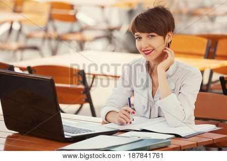 Young fashion business woman using laptop at sidewalk cafe. Stylish female model in white blouse