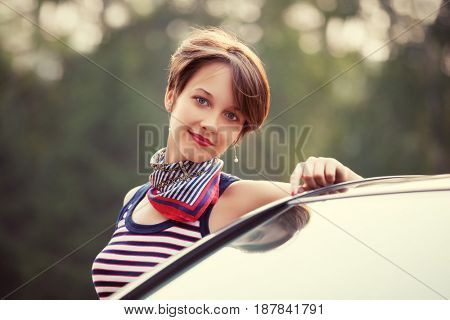 Happy young fashion woman next to her car. Stylish female model in tank top outdoor