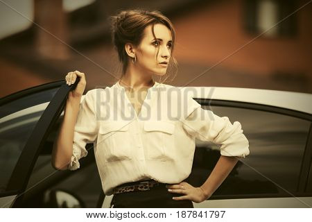 Young fashion business woman standing beside her car. Stylish female model in white blouse outdoor