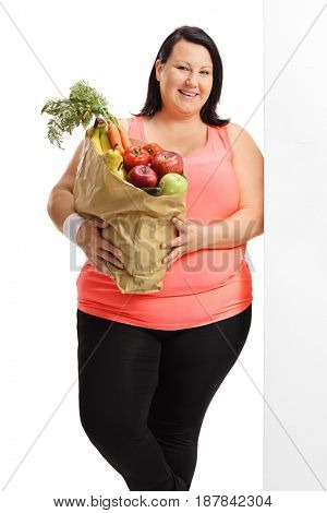 Woman with a bag filled with groceries leaning against a wall isolated on white background