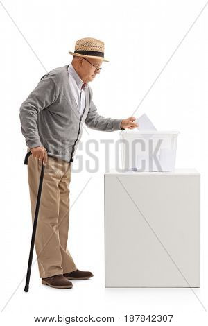 Full length profile shot of an elderly man putting a ballot into a voting box isolated on white background