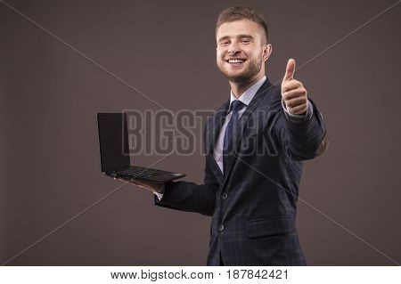 Man in suit with laptop in his hands shows OK sign