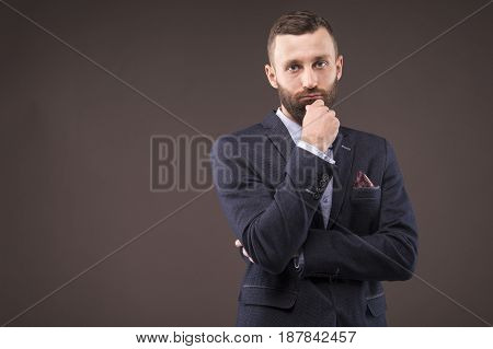 Confident man leaned his hand to his beard and looking at the camera