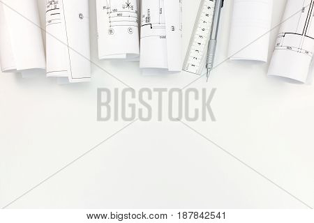 Rolls With Architectural Plans, Mechanic Pencil And Ruler On White Background