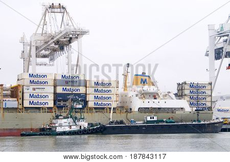 Oakland CA - May 23 2017: Tugboat POINT VINCENT securing a barge next to Matson cargo ship KAUAI to provide maritime services while the vesse is docked loading at the Port of Oakland.