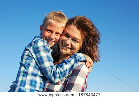 Beautiful mum with cute little child on her back. Parent and child smile enjoy life and looking to camera. Closeup.