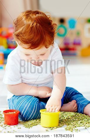 Cute Redhead Baby Boy Developing His Fine Motility Skills By Playing With Green Peas At Home